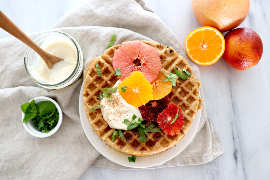 White plate with winter citrus spiced waffles topped with sliced winter fruit. Citrus around photo.