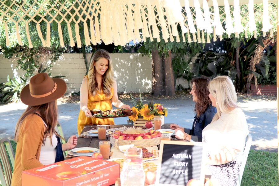 Blogger Potluck with women sitting at table outside eating apple themed dishes
