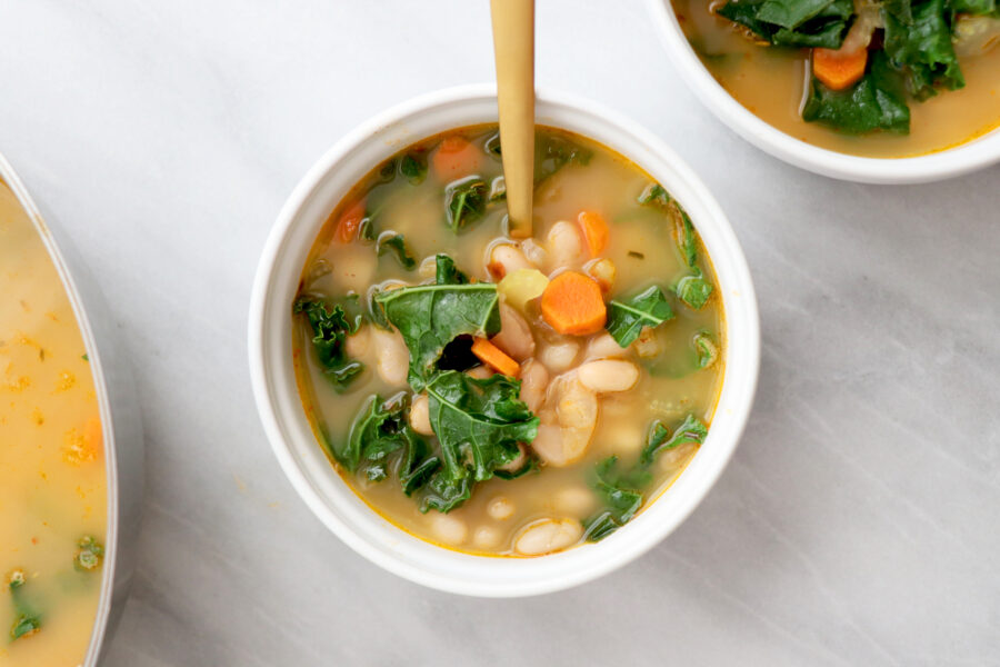 Kale, White Bean & Carrot Soup in White Bowl with Gold Spoon