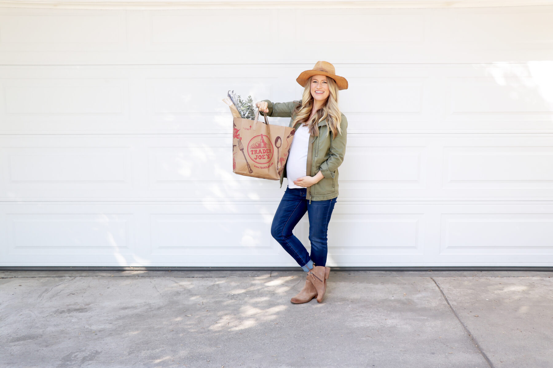 Blonde Pregnant Woman in Green Coat, White Shirt, Denim Jeans, Tan Boots and Straw Hat holding Trader Joes Grocery Bag in front of White Garage Door