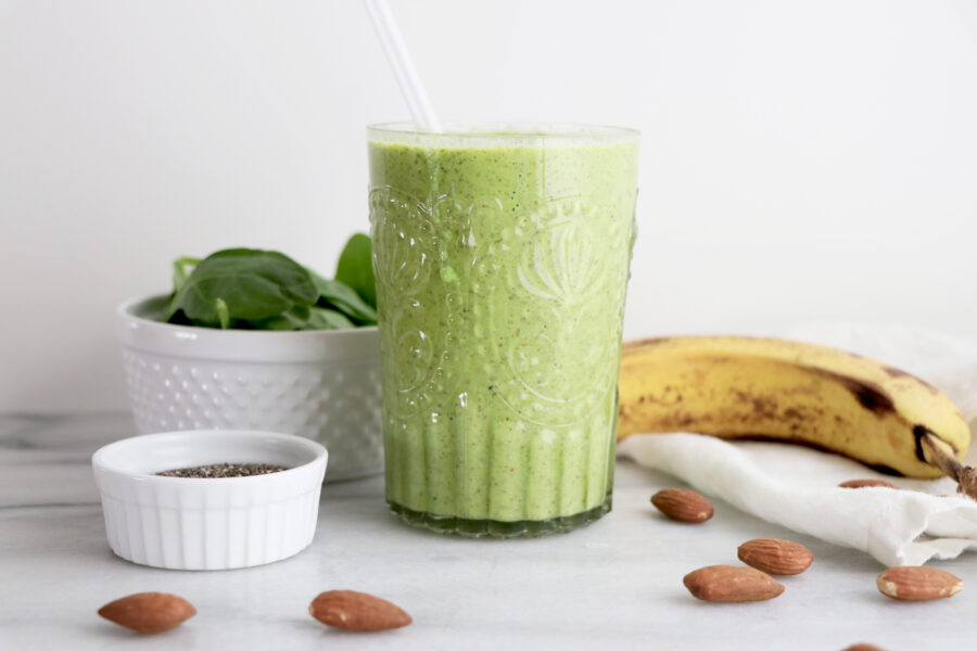 Green Smoothie In Glass with almonds, spinach and banana next to glass