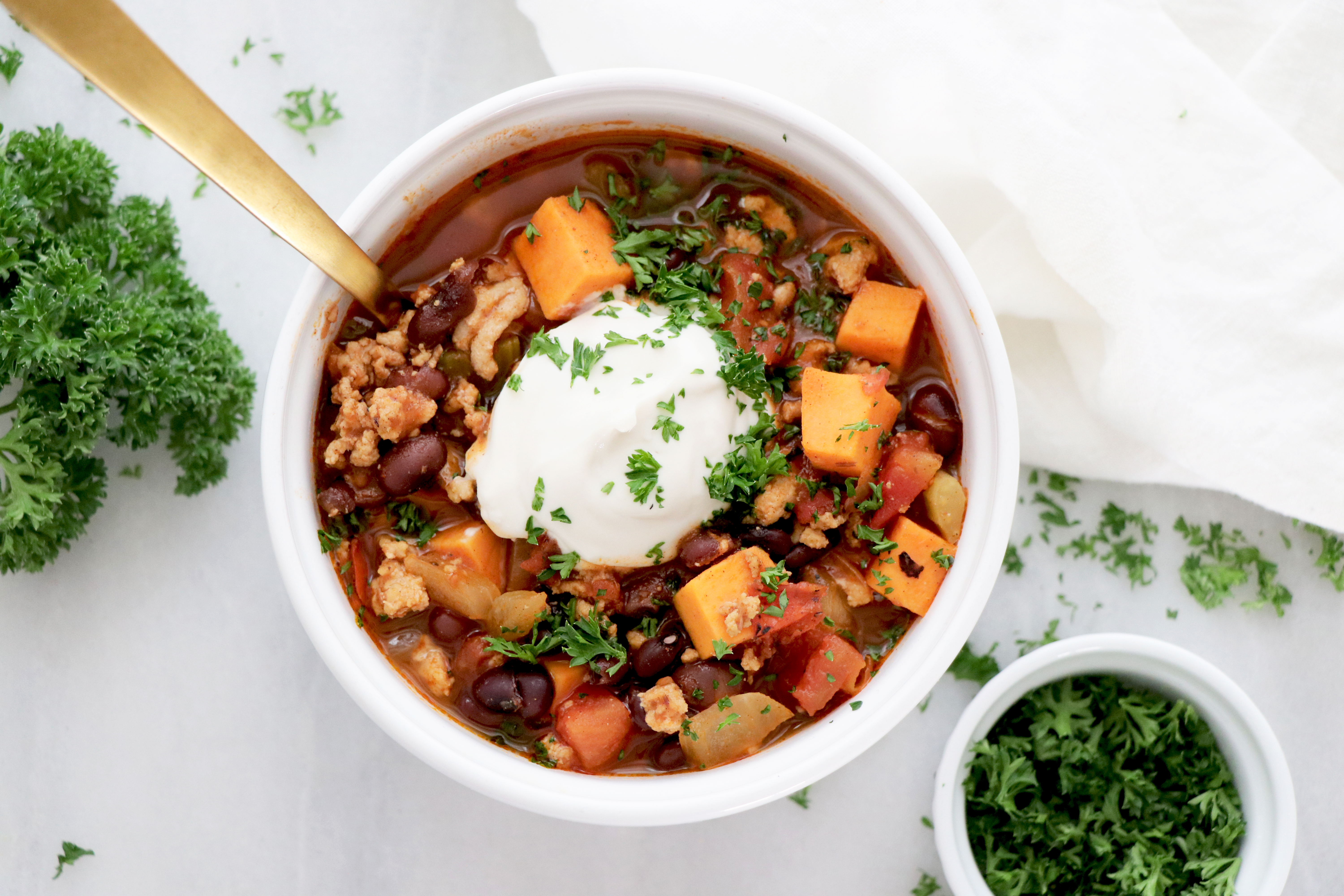 Chili in white bowl with dairy-free sour cream and green herbs