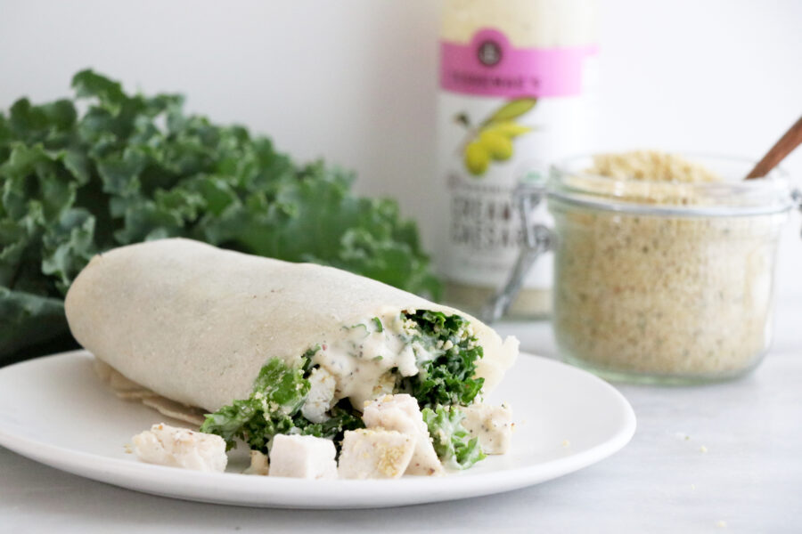 Kale, chicken and dairy-free caesar dressing in cassava flour tortilla on plate
