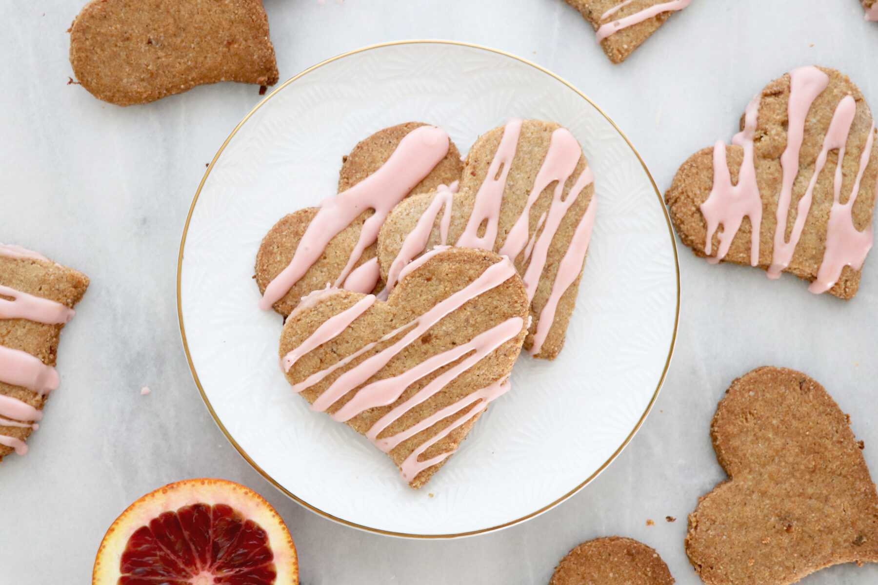 Heart shaped cookies with pink icing on top. Slice of blood orange in background.