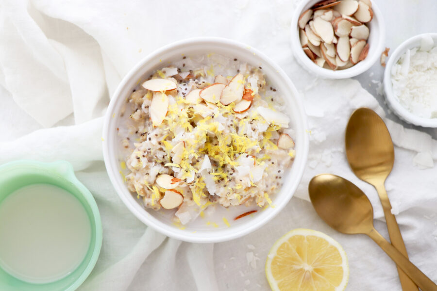 White bowl with oatmeal topped with sliced almonds and gold spoon on side.