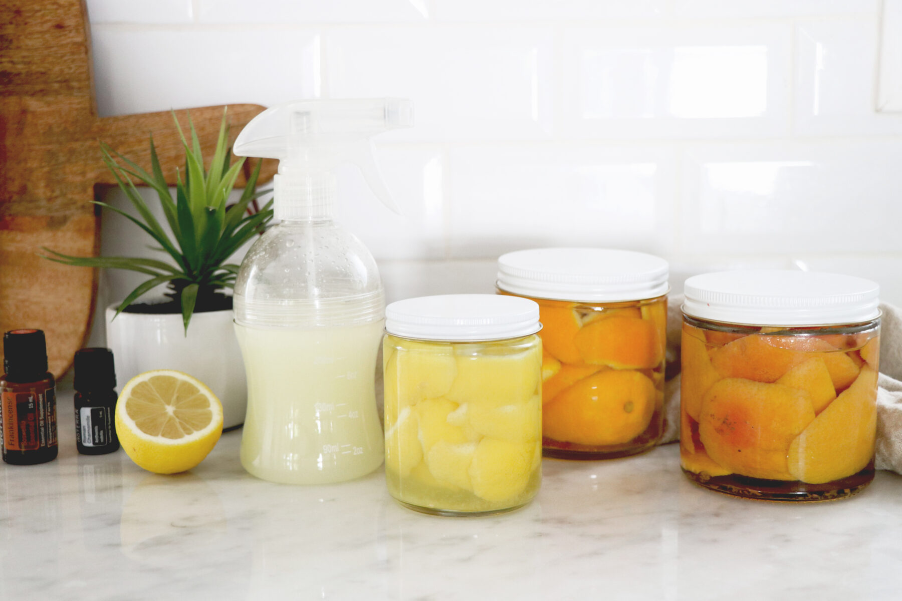 3 clear jars with citrus cleaner and one spray bottle all on countertop.