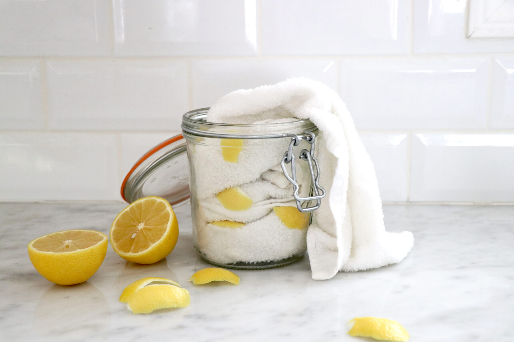 Glass jar filled with white towels and lemon slices with lemon on the side.