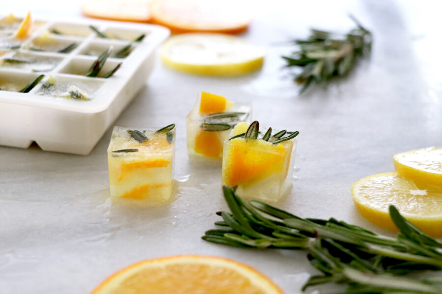 DIY disposal rosemary citrus cubes with cube tray, citrus slices and rosemary in the background.