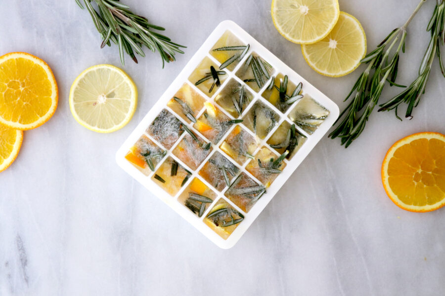 Ice cube tray filled with DIY Citrus rosemary cleaner with lemon slices and rosemary on the side.