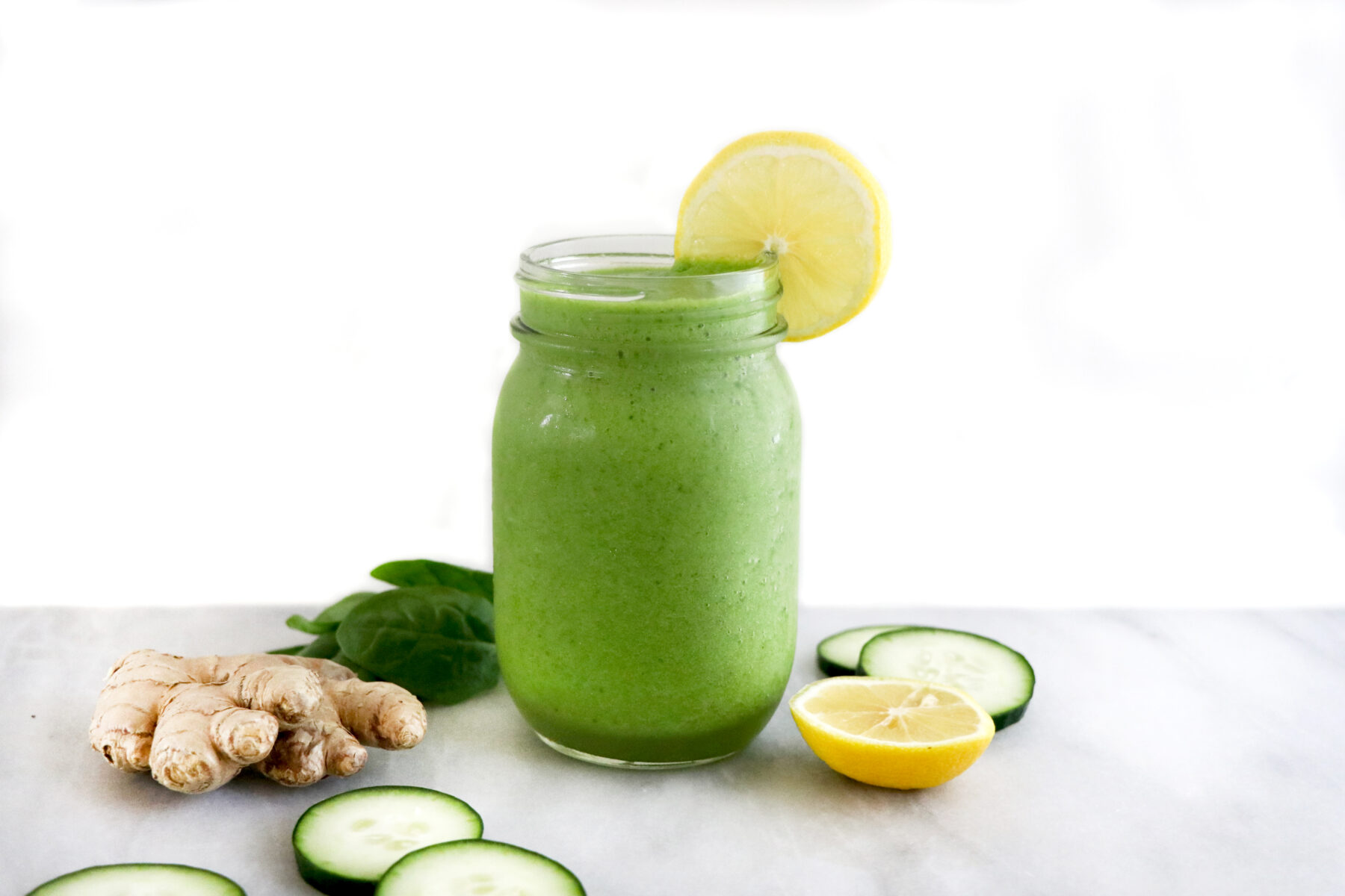 Mason jar filled with green smoothie and lemon slice on top. Surrounded by ginger, cucumber, spinach and citrus.