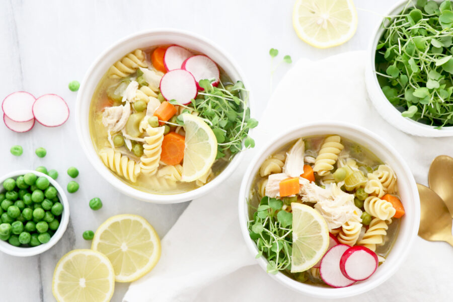 Two bowls of lemon chicken soup filled with veggies and vegetable slices surrounding bowls.