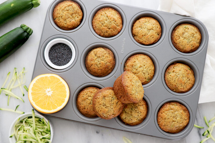Orange zucchini muffins in silver muffin tin with two on top and orange slice on the side.