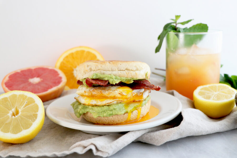 Breakfast sandwich with turkey bacon, fried egg and avocado. Orange grapefruit juice and citrus slices.