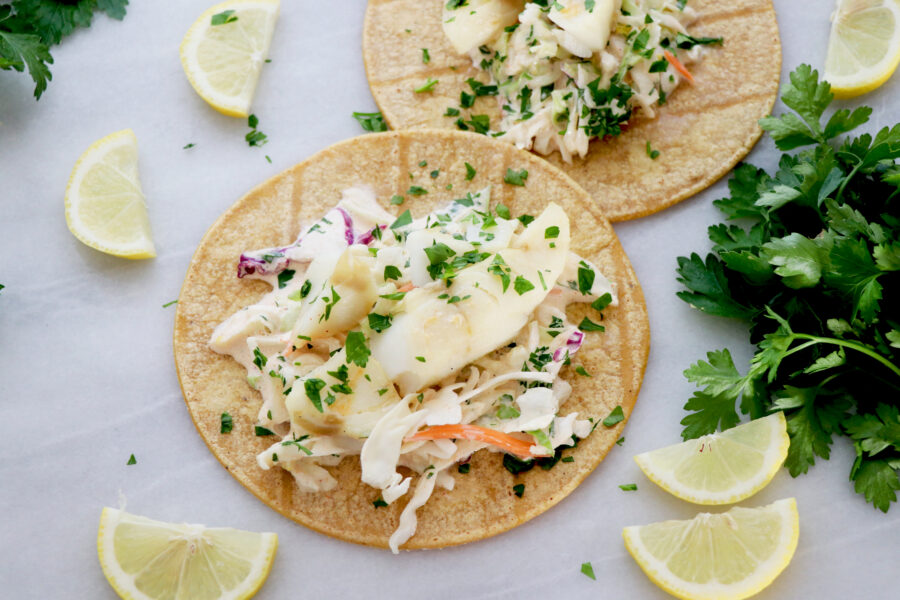 Two corn tortillas topped with citrus fish, homemade slaw. Surrounded by lemon slices and cilantro.