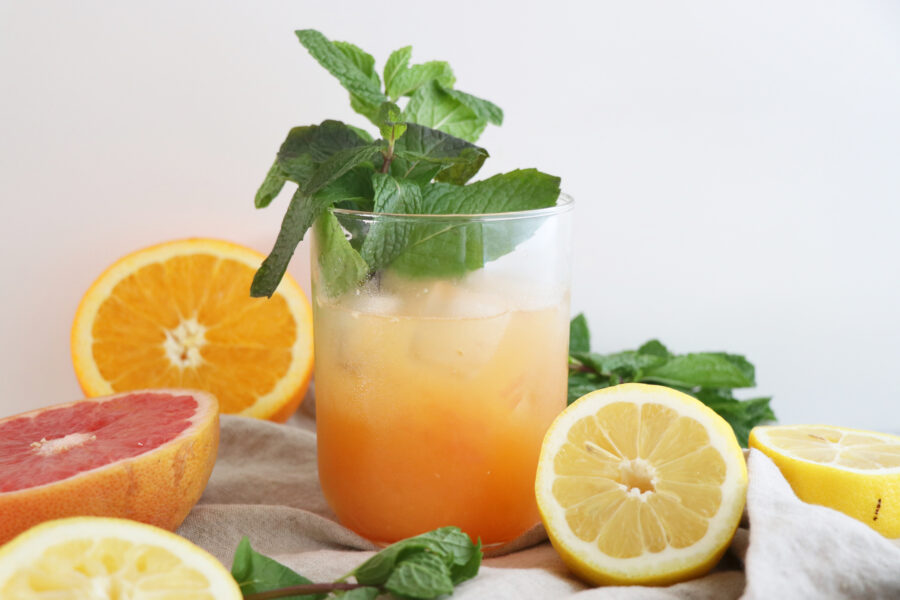 Glass of juice with citrus slices and basil.