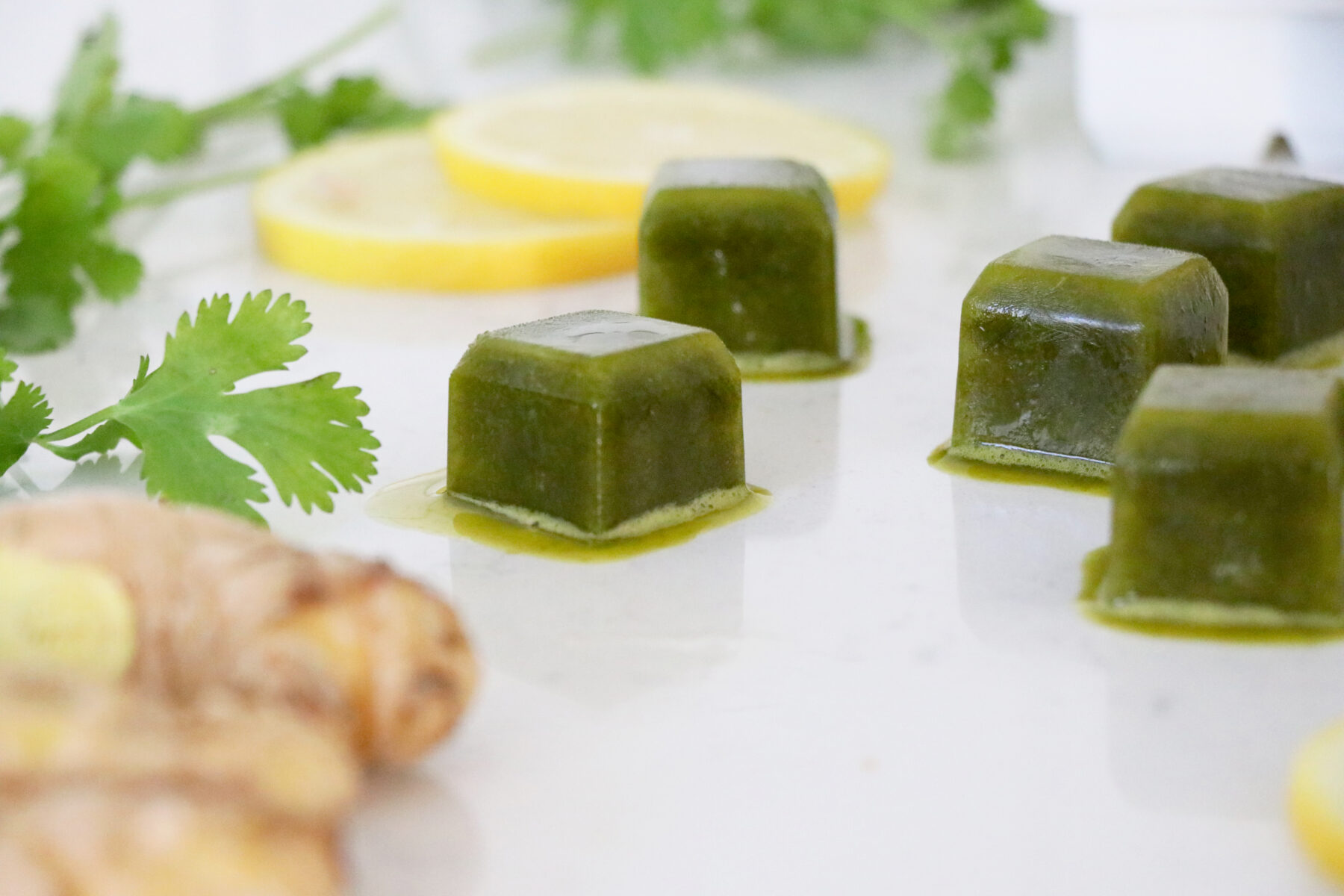 Frozen smoothie cubes, ginger, lemon slices and cilantro.