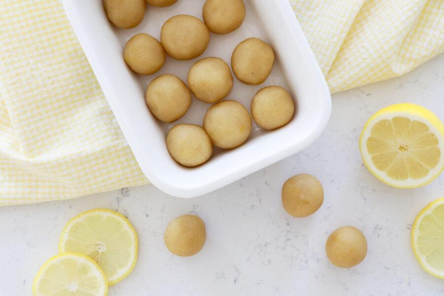 Lemon cookie dough bites with slices of lemon.