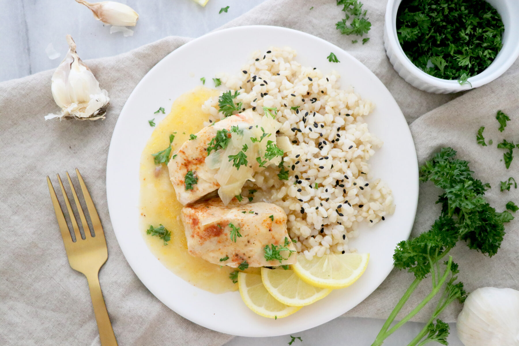 White plate of lemon garlic chicken with sauce, brown rice and lemon slices.