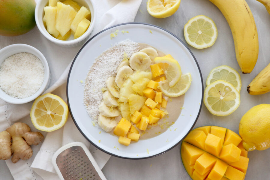 White bowl filled with smoothie bowl and topped with sliced banana, shredded coconut, mango and pineapple. Fruit surrounding bowl.