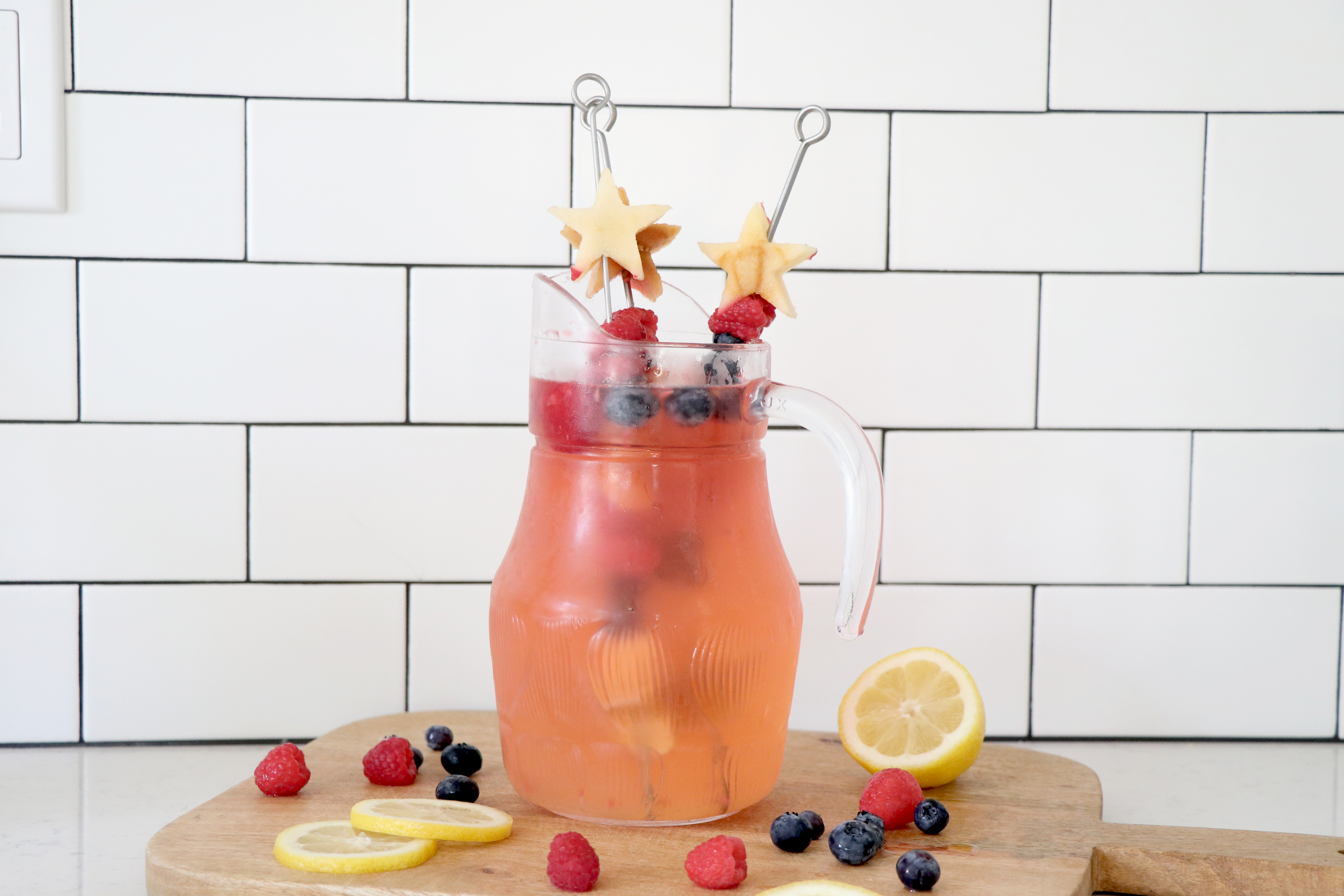 Lemon, raspberry and blueberry infused lemonade in clear pitcher.