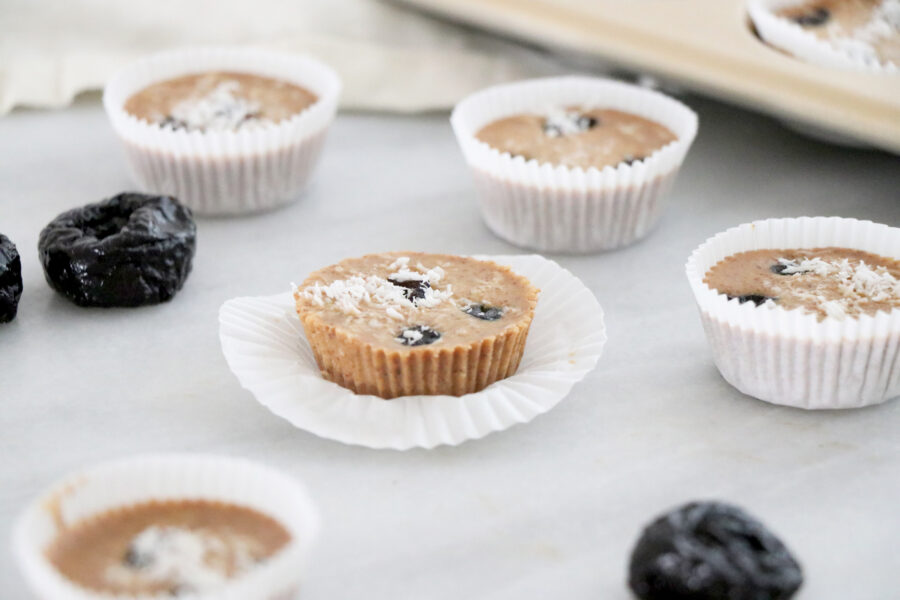 Almond butter prune cups on counter with prunes next to them.