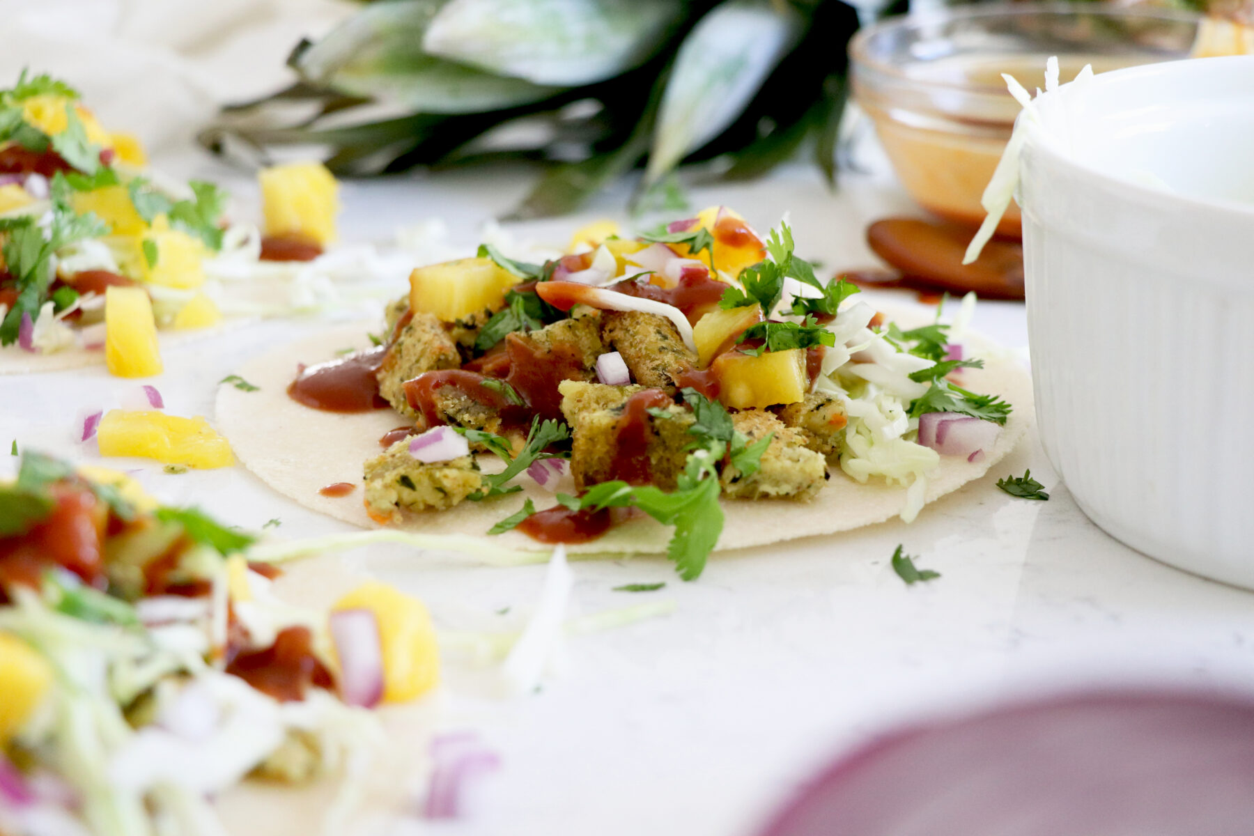 BBQ pineapple tacos with crumbled veggie burger. Pineapple in the background.