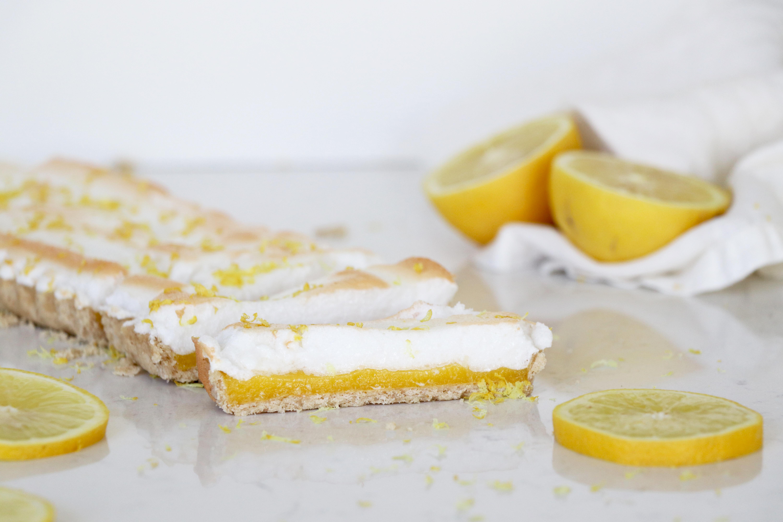 Lemon meringue tart on counter with sliced lemon.