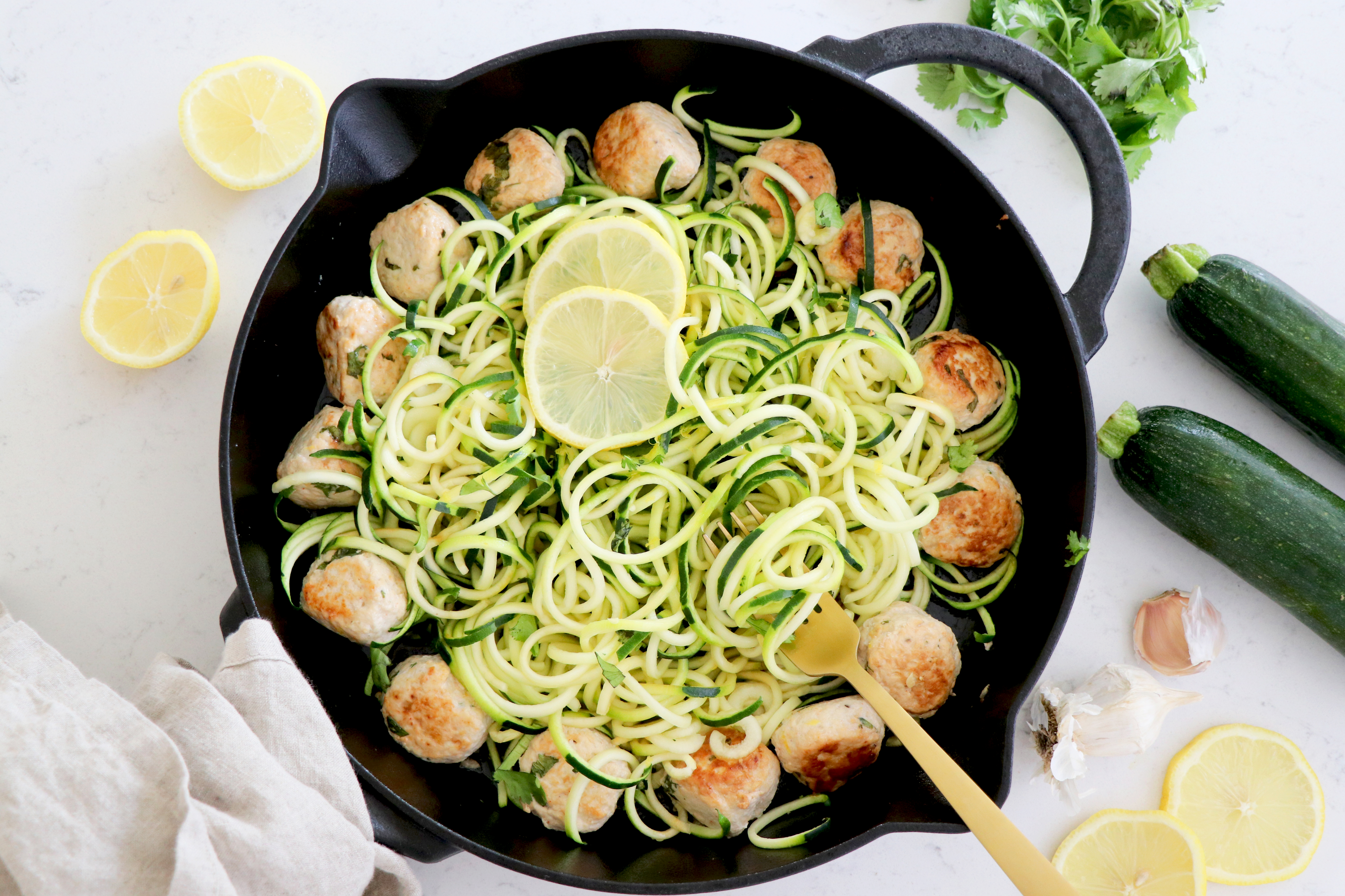 Turkey meatballs with zucchini noodles and lemon on cast iron pan.