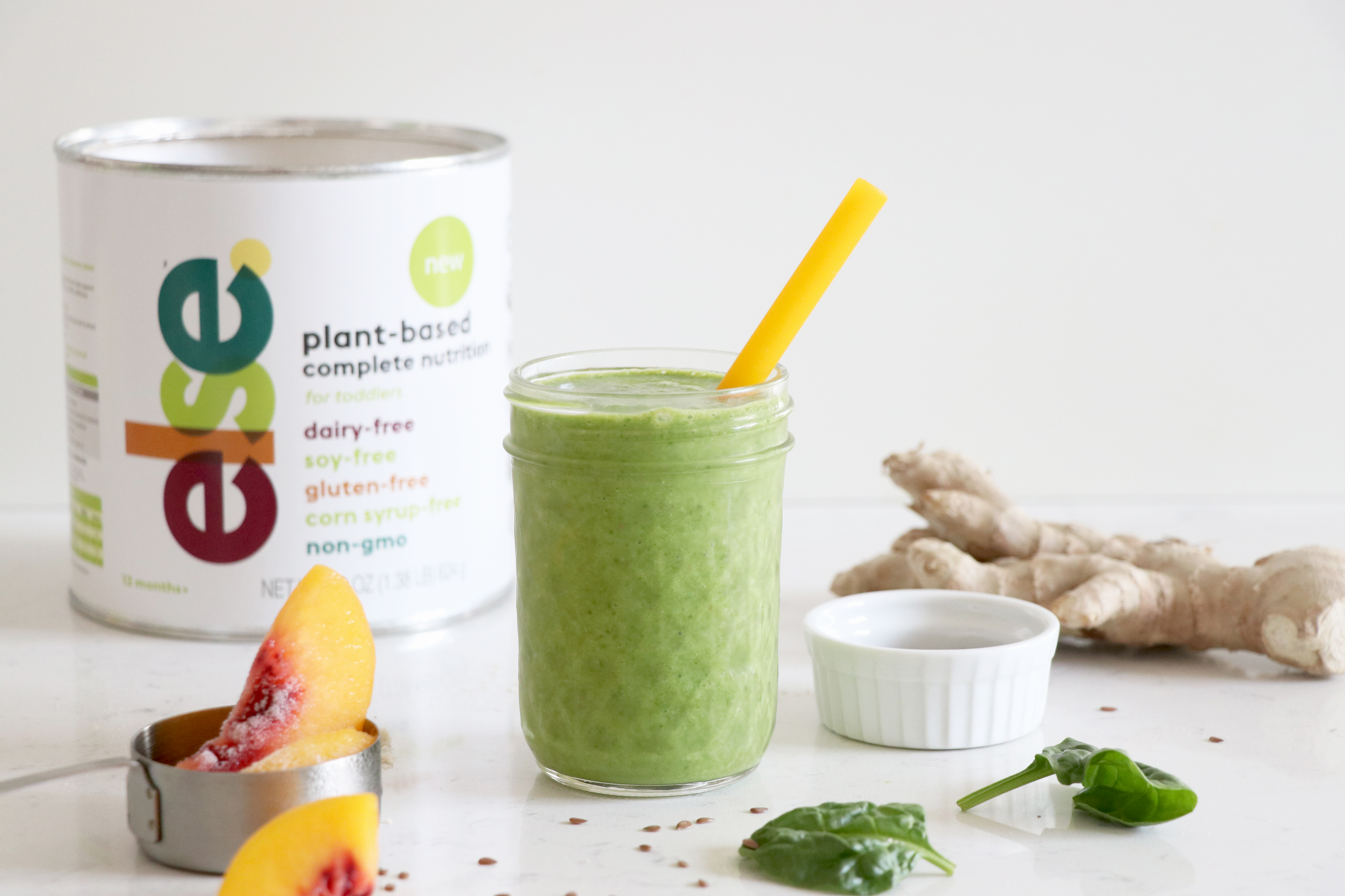 Green smoothie with yellow straw and container of complete nutrition for kids.