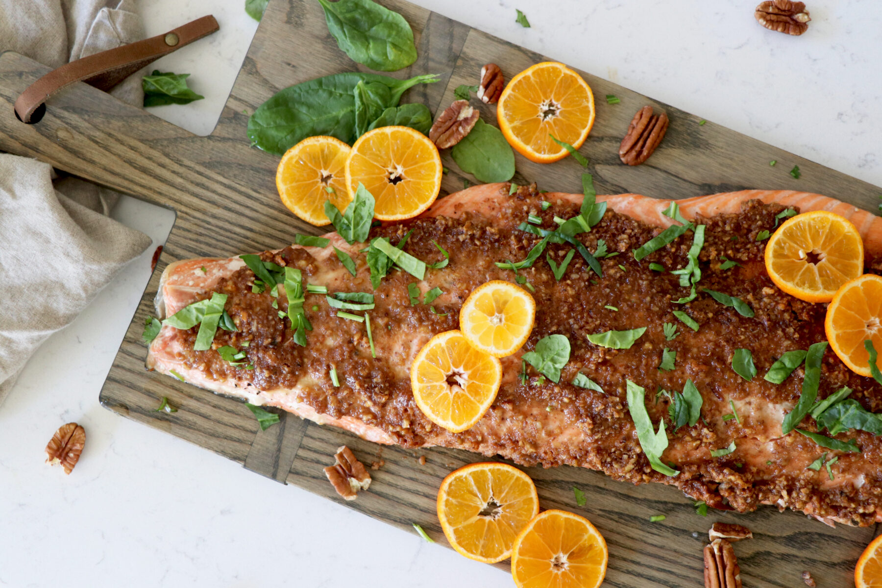 Pecan crusted salmon on grey wooden slab with orange slices.