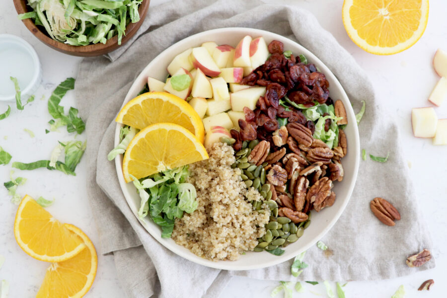 Harvest bowl with greens, pecans, orange slices, quinoa and diced apples.