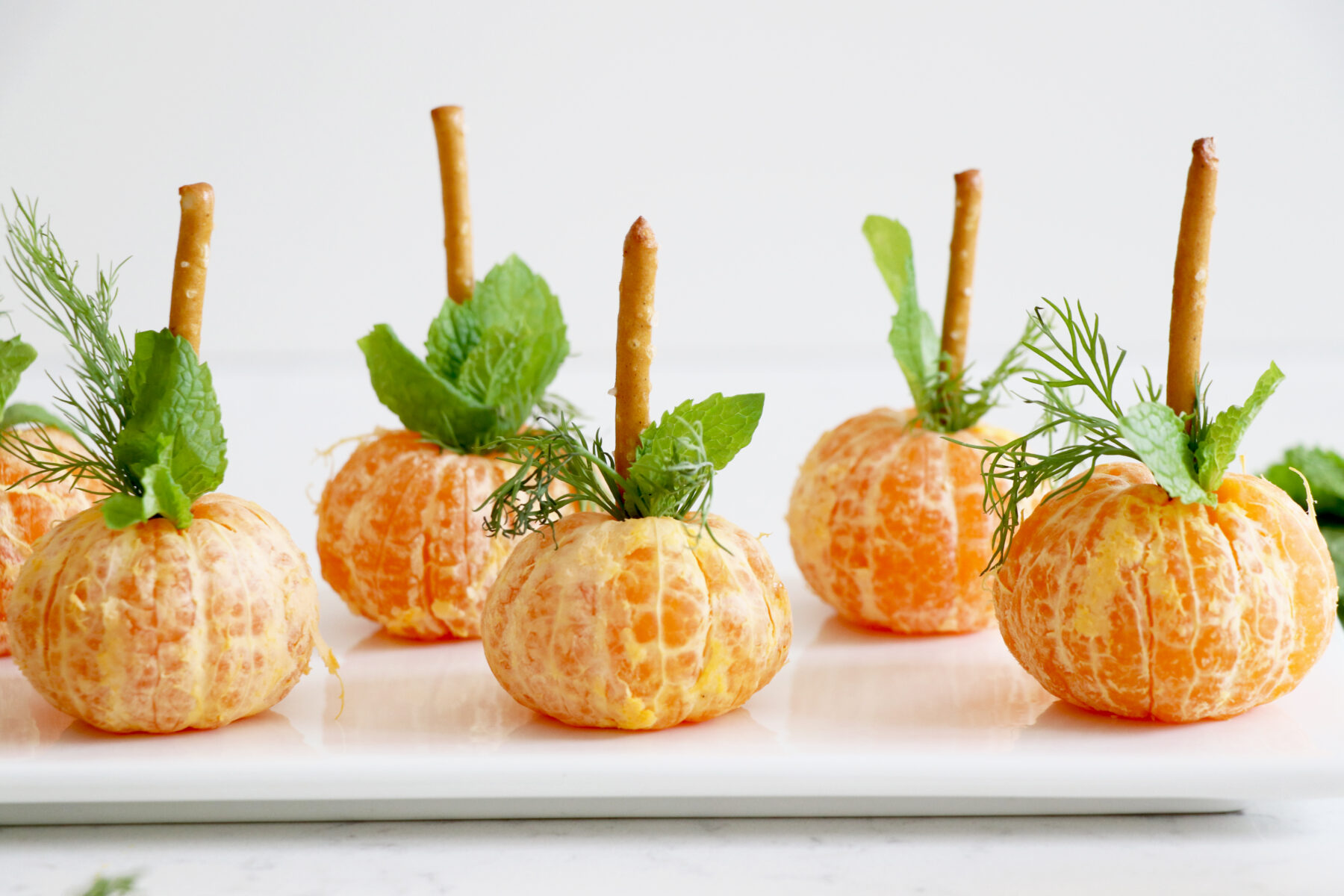 Oranges topped with pretzel and greens on white plate.