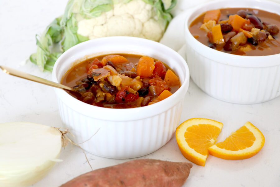 Two white bowls of sweet potato chili surrounded by orange slices, cauliflower and sweet potato.