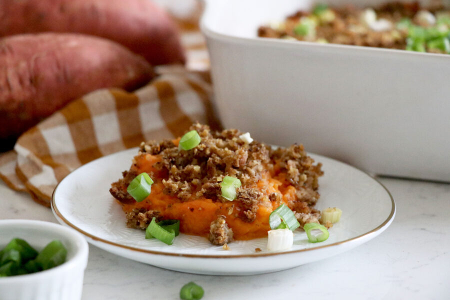 Plate with piece of sweet potato casserole and casserole dish In background.