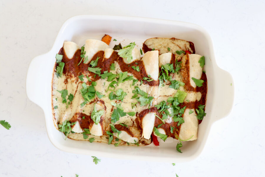 Baking dish with enchiladas covered with a red mole sauce and cashew cream sauce.