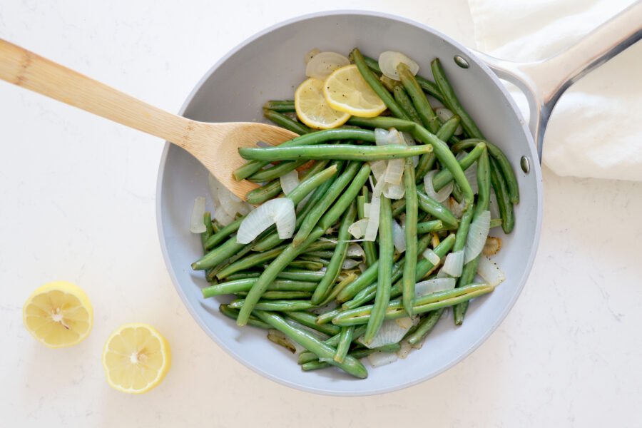 Saute pan with green beans and lemon slices.