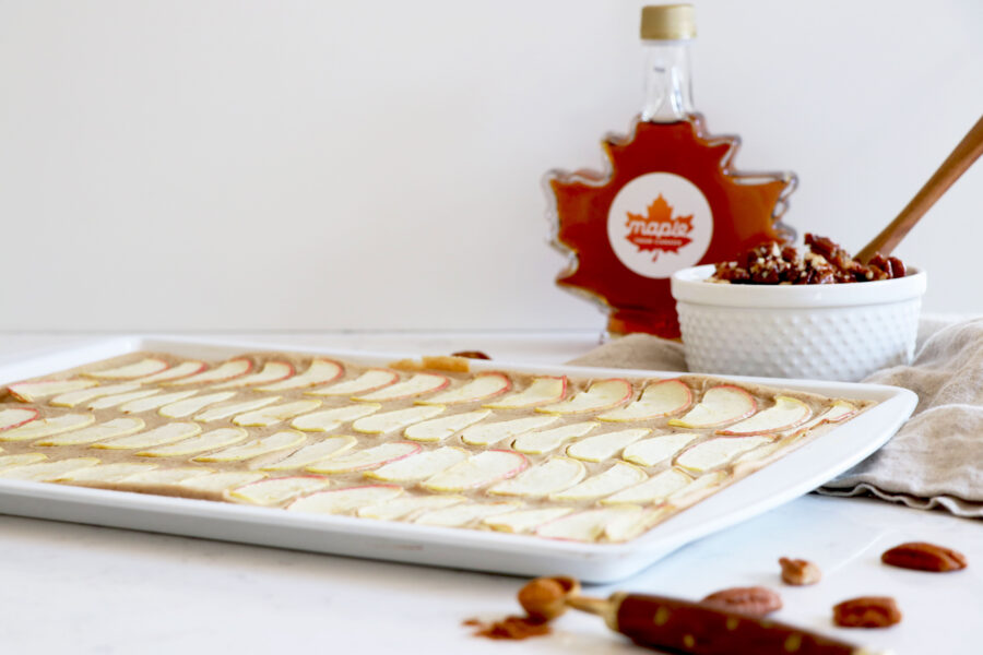 Sheet pan with pancakes and maple syrup in background.