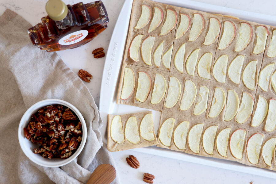 Sheet pan with pancakes topped with apple slices, pecans and maple syrup.