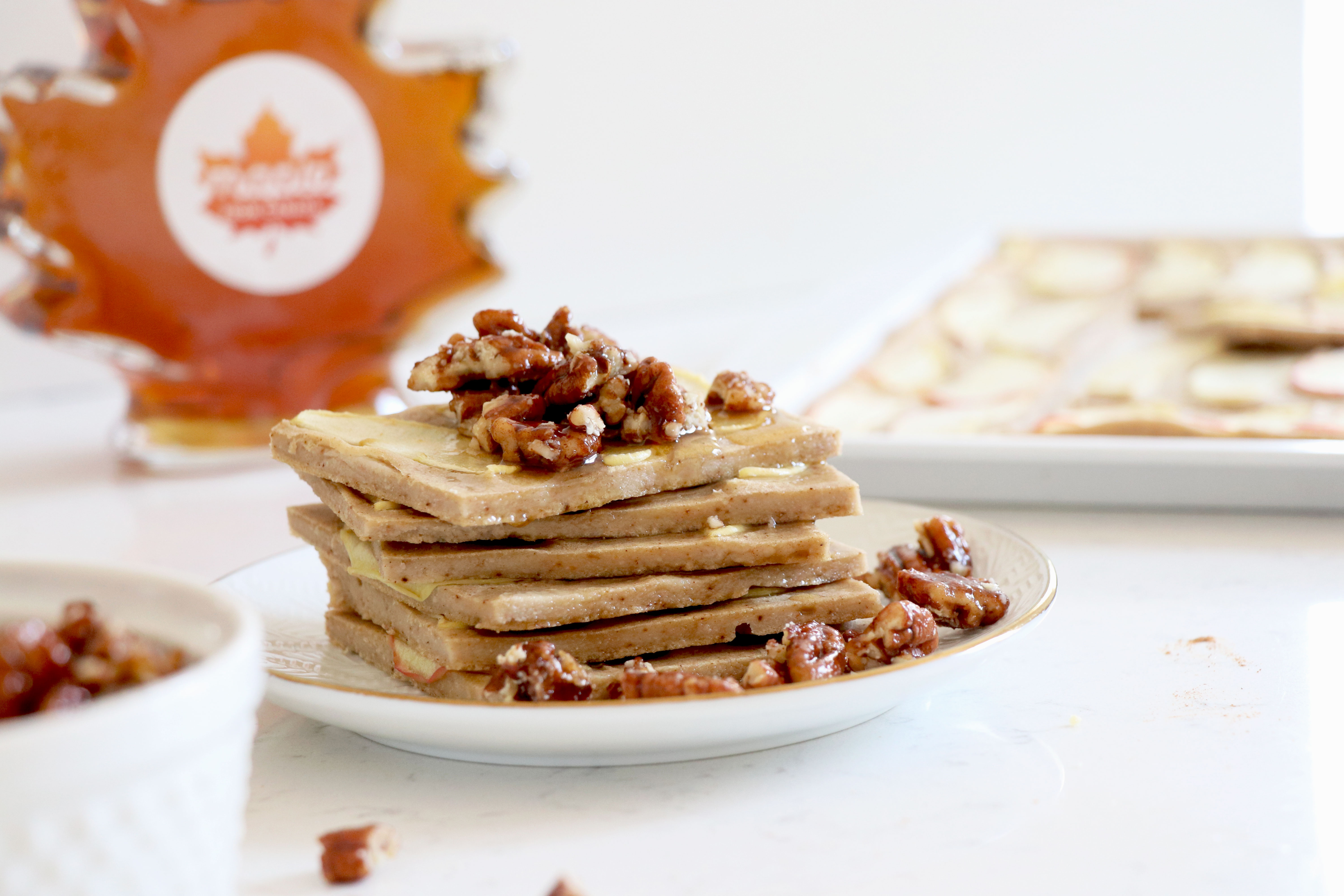Plate with pancakes topped with pecans.