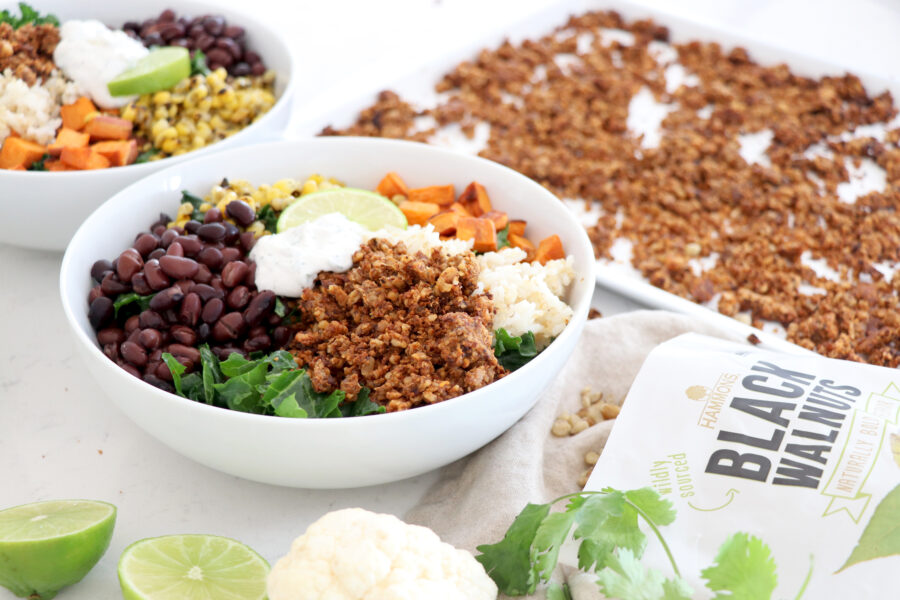 White bowl with vegan burrito bowl fillings and walnut meat on the side.