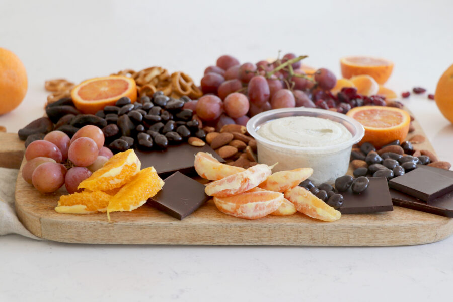 Wooden plank with a variety of fruit, vegan spreads and citrus.
