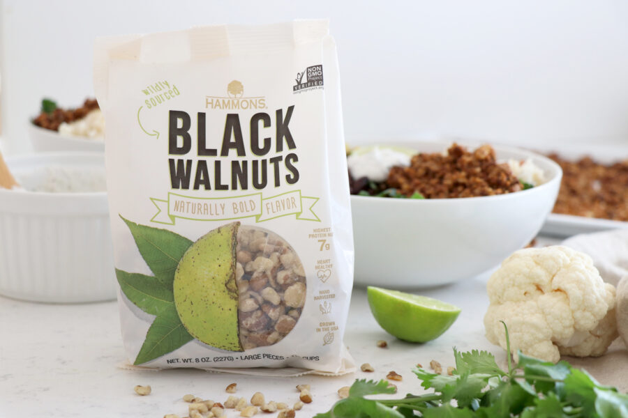 Package of black walnuts with burrito bowl in background.