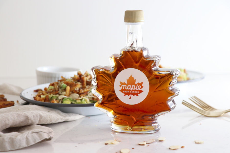 Maple From Canada syrup bottle with salad in the background.