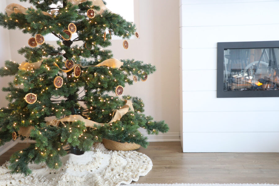 Christmas tree with dried orange ornaments and fireplace in background.