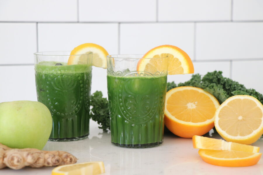 Two glasses of green juice with sliced orange.