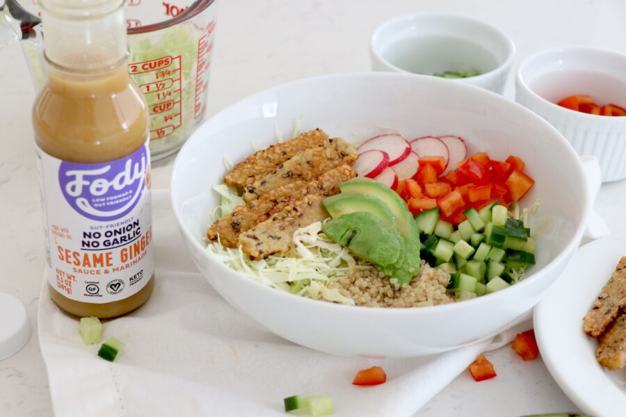 White bowl with low fodmap foods and dressing on the side.