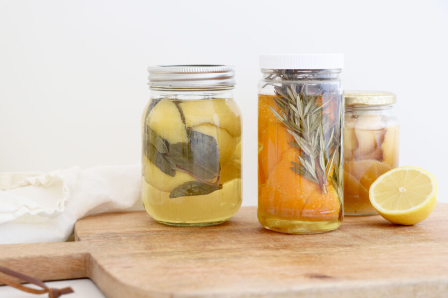 Mason jars with citrus and herbs for cleaning.