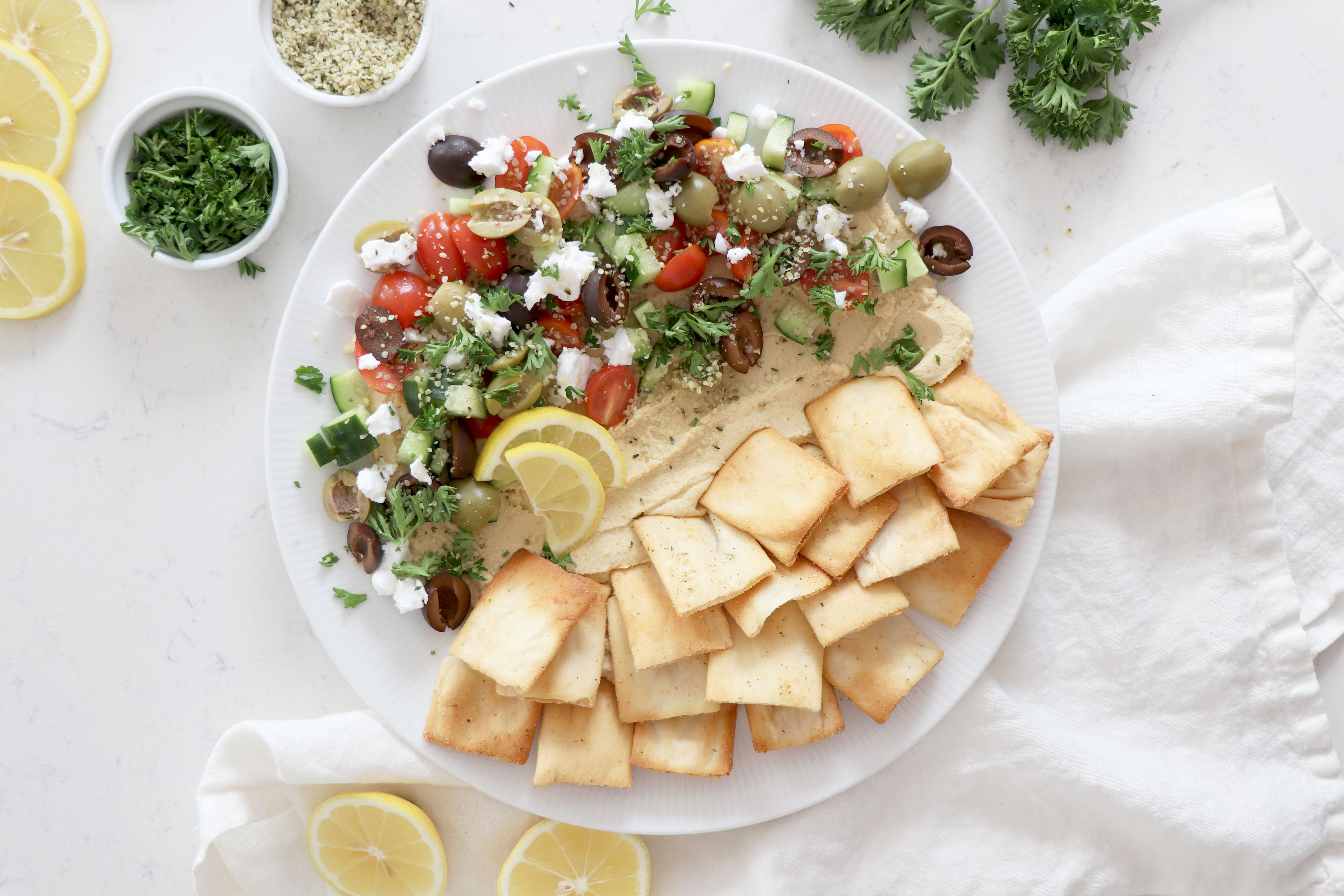White plate with hummus, diced veggies and crackers. Surrounded by parsley and sliced lemon.