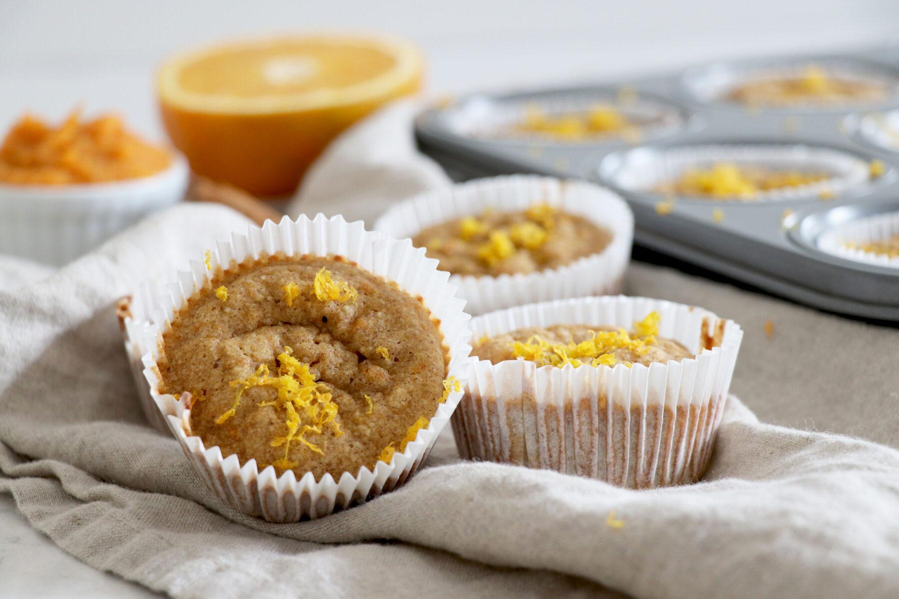 Orange cinnamon muffins with muffin tin behind and sliced orange.