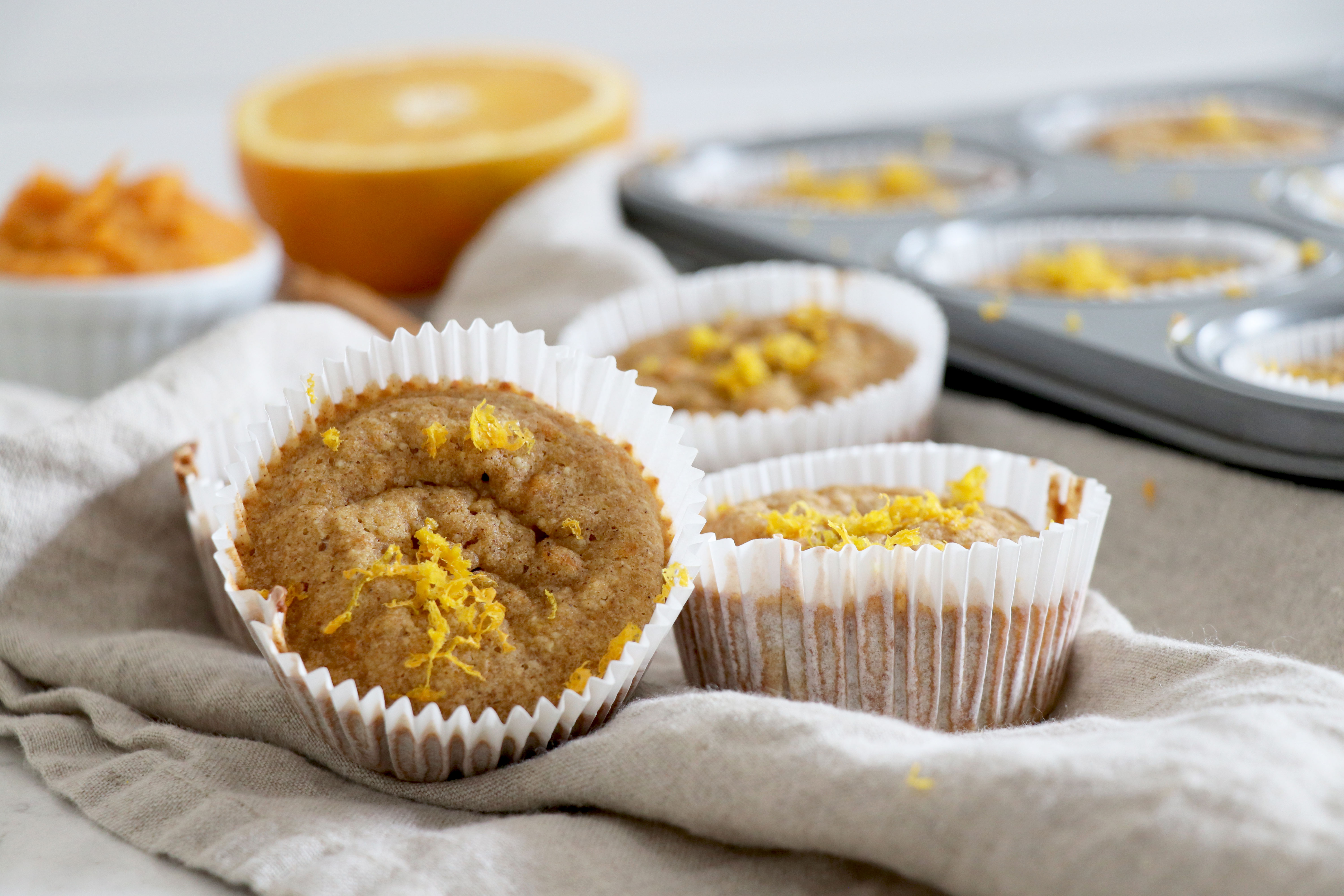 Orange cinnamon muffins with muffin tin behind and sliced orange.